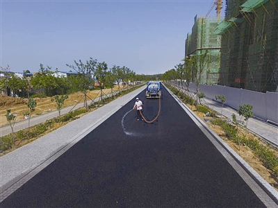 """位于青岛中德生态园首条""""海绵道路""""——生态园9号线建成."""